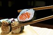 Maki sushi with salmon held in chopsticks