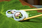 Fish rolls with cucumbers and tuna on a leaf