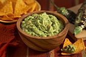 Guacamole in a Wooden Bowl; Tortilla Chips; Charred Jalapeno Peppers