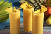 Papaya, Banana, Pineapple Smoothies in Glasses with Fresh Fruit Garnish