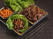 Oriental pork with carrot strips on lettuce leaves