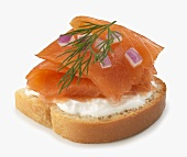 Slice of Bread Topped with Cream Cheese and Smoked Salmon; Red Onion and Dill; White Background