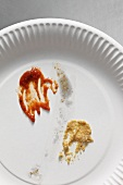 Left over ketchup and mustard on a paper plate