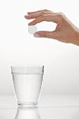Hand hält Brausetablette über Wasserglas