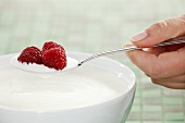 Hand holding a spoon of yogurt with raspberries