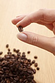 Fingers holding a coffee bean