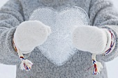 Person wearing mittens holding an ice heart