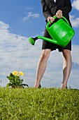 Woman with a green watering can