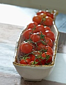 Tomatoes (still on the stem) in a ceramic dish