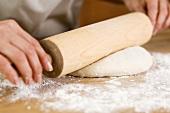 Frau rollt Teig mit einem Nudelholz aus