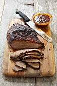 Partially Sliced Barbecue Brisket on a Cutting Board; Knife and Barbecue Sauce