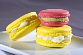 Yellow macaroons with vanilla cream, pink macaroon with pistachio cream