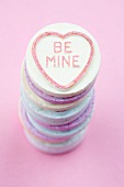 Stacked brightly colored candies with 'Be Mine' written on them