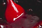 Stirring red fruit jelly