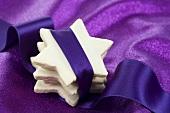 Gestapelte Zimtsterne in ein violettes Band gewickelt