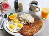 Large Breakfast of Sunny Side Up Eggs, Chicken Fried Steak with Gravy, Hash Browns, Coffee and Juice