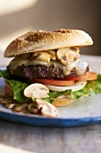 Swiss Cheese Burger with Mushrooms, Tomato, Onion and Lettuce on Sesame Seed Bun