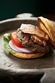 Grilled Hamburger with Bacon, Tomato, Onion and Lettuce on a Toasted Bun