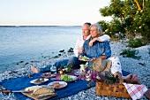 Älteres Pärchen beim Picknick am Strand
