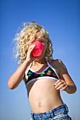 Kleines Mädchen im Bikini-Top trinkt aus Plastikbecher