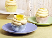 Frosted Cupcakes with Lemon Curd; On Blue, Green and White Plates