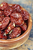 A bowl of dried tomatoes in a ceramic bowl