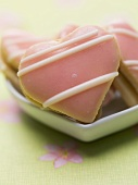 A bowl of pink heart biscuits filled with jam