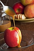 Caramel sauce being poured over an apple