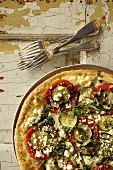 Thin Crust Pizza Topped with Zucchini, Tomatoes, Feta Cheese and Fresh Basil; From Above