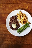 Grilled Steak with French Fries and Green Beans on a White Plate; From Above