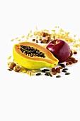 Ingredients for müsli: papaya, apple, nuts, pumpkin seeds and raisins