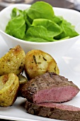 Fried ostrich fillet with spinach salad and rosemary potatoes