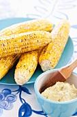 Gegrillte Maiskolben auf blauem Teller, Butter und Backpinsel