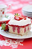 Piece of Strawberry Poke Cake with Whipped Cream