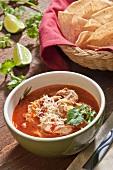 Bowl of Chicken Tortilla Soup; Cilantro Garnish; Basket of Tortilla Chips