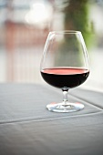 Glass of Red Wine on a Table with a White Table Cloth