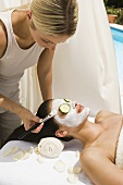 A beautician applying a face mask to a womans face