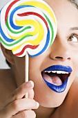A woman holding a colourful lollipop