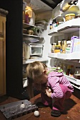 A girl in front of a fridge picking up dropped eggs