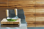 A chopping knife and herbs on a chopping board