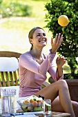 A woman throwing grapefruit