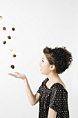 A woman throwing chocolates in the air