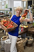 Woman in grocery store with tomatoes