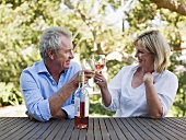 A couple toasting with wine outdoors