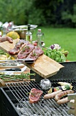 Steaks being placed on a barbeque.