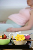 Bowls of fruit on a tray with a pregnant woman in the background