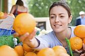Frau bei der Auswahl von Orangen