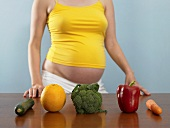 A pregnant woman with fruit and vegetables