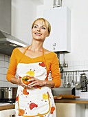 A housewife in a kitchen holding a pepper
