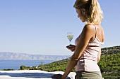 Frau hält ein Glas Weisswein mit Ausblick auf einen See